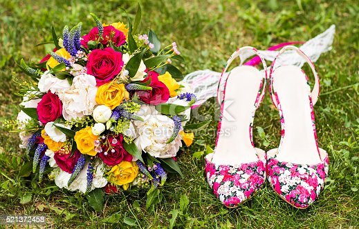istock wedding bouquet and shoes on the grass 521372458