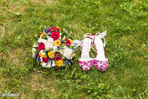istock wedding bouquet and shoes on the grass 521603014