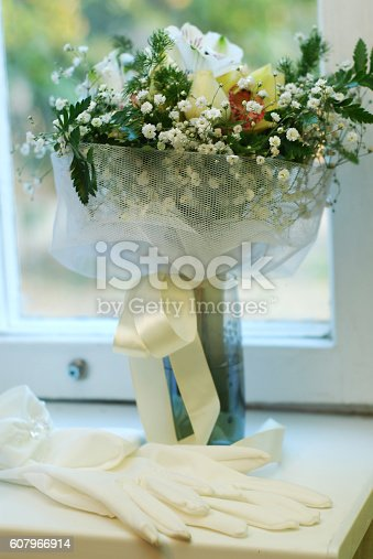 beautiful wedding bouquet with white gloves by window sill