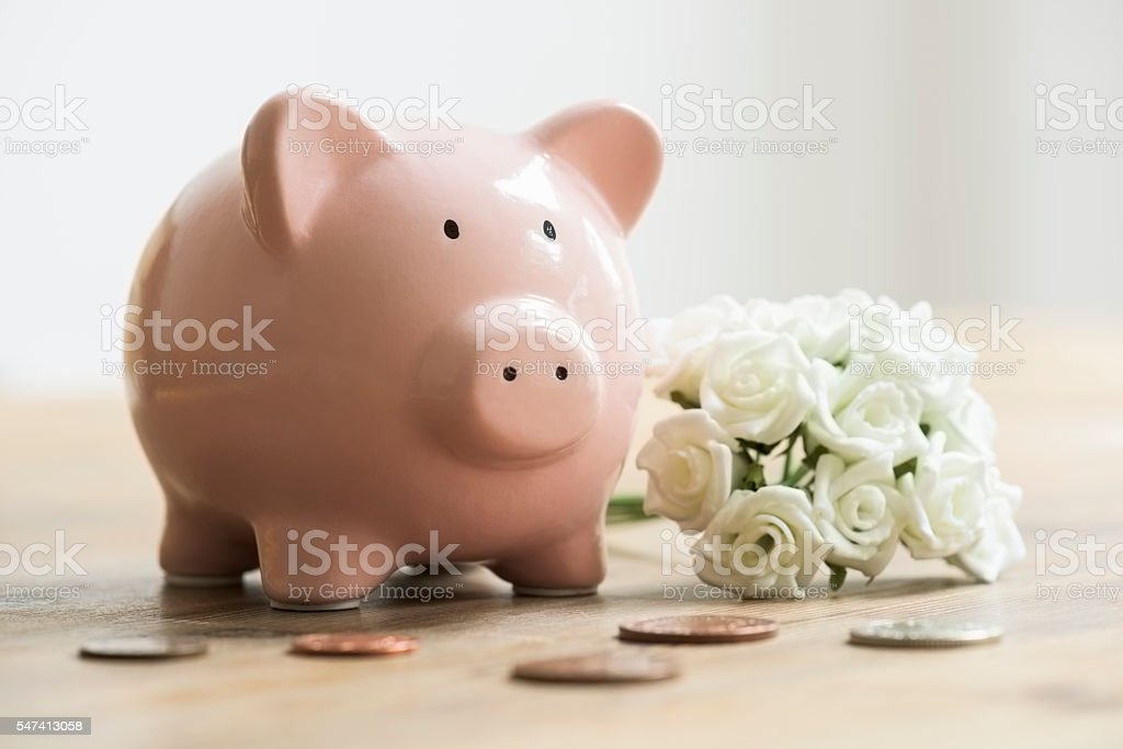 Wedding bouquet beside piggy bank and coins for saving stock photo