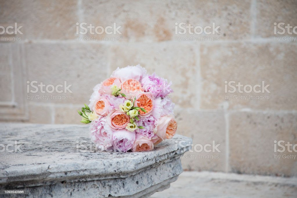 Wedding Bouquet From Orange Roses Pink Peonies And Cream Flowers Lies On Stone Table Before The Wedding Ceremony Stock Photo Download Image Now Istock