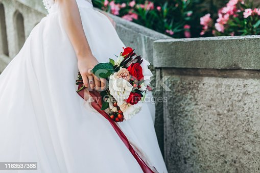 istock Wedding bouquet in bride's hand. 1163537368