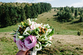Wedding bouquet in bride's hands. Field view, place for text.