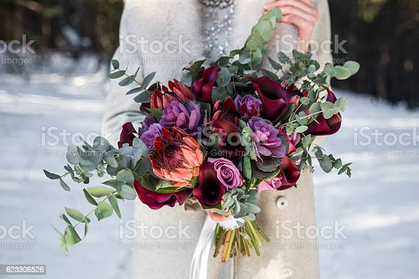 Wedding bouquet in hands of the bride. Winter time, snowy fores