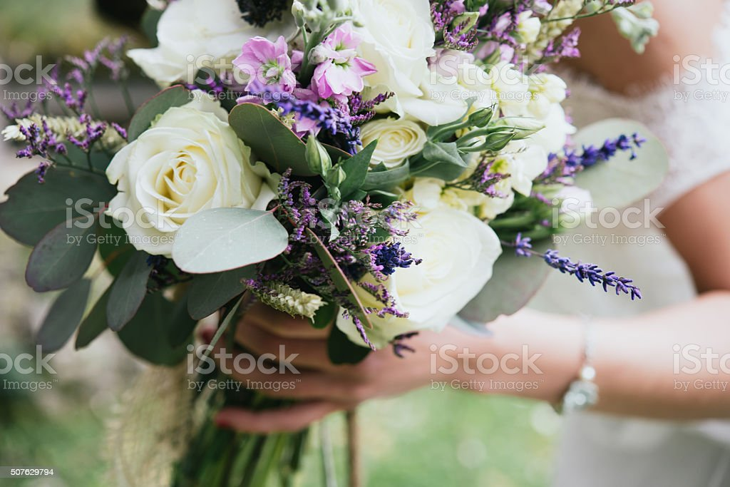 Wedding bouquet in the hand of her bride stock photo