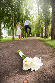 Wedding bouquet lying on the ground and newlyweds leaving