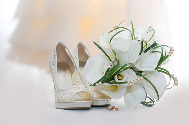 hochzeit bouquet von calla-lilien und braut schuhe - goldhochzeitsschuhe stock-fotos und bilder