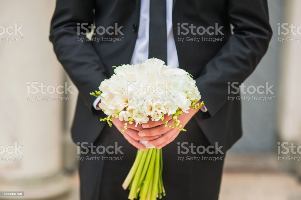 Wedding bouquet of lilies.The bridegroom holds a bunch of white roses in her hands. stock photo