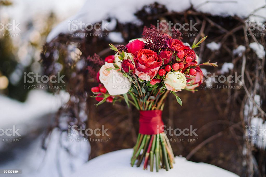 wedding bouquet of red and white flowers on snow stock photo