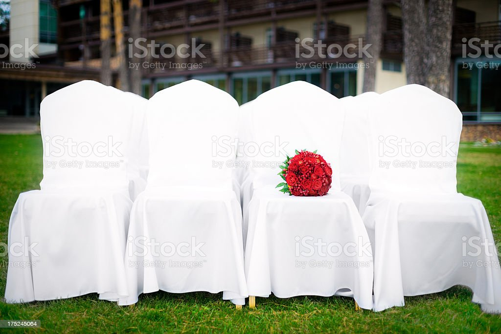 Wedding bouquet of red flowers on white chairs royalty-free stock photo