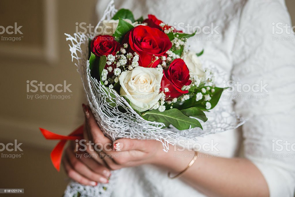 Wedding bouquet of red roses in bride's hands with stock photo
