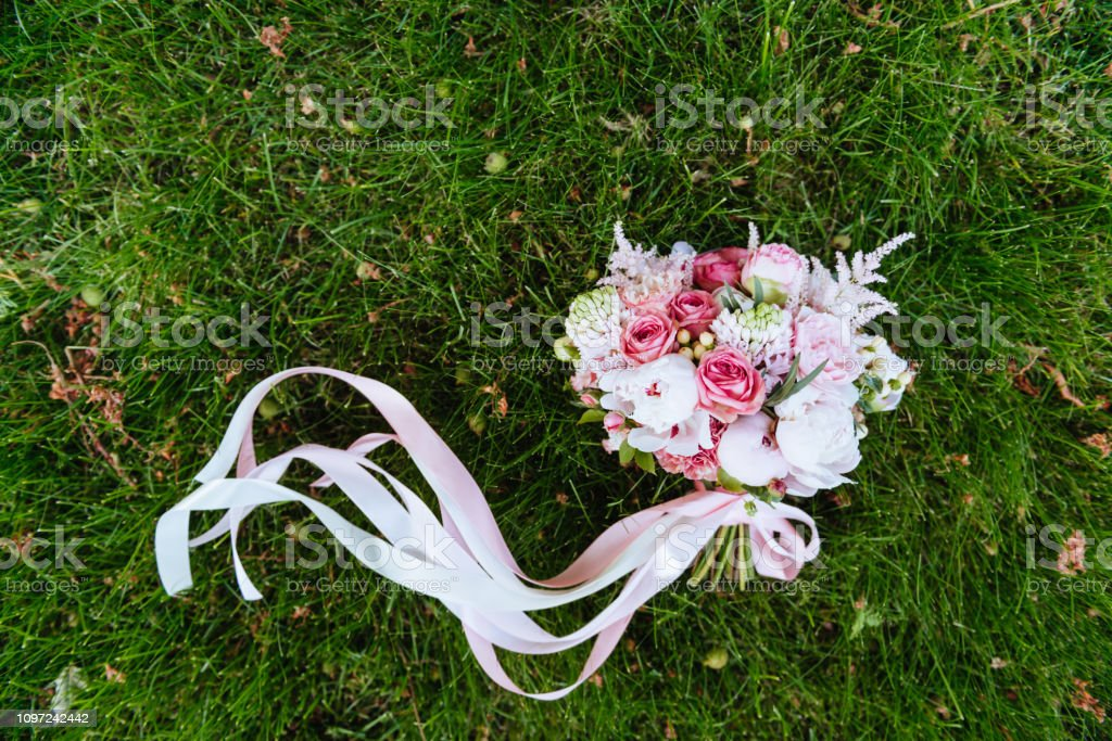 Wedding bouquet of roses on green grass stock photo