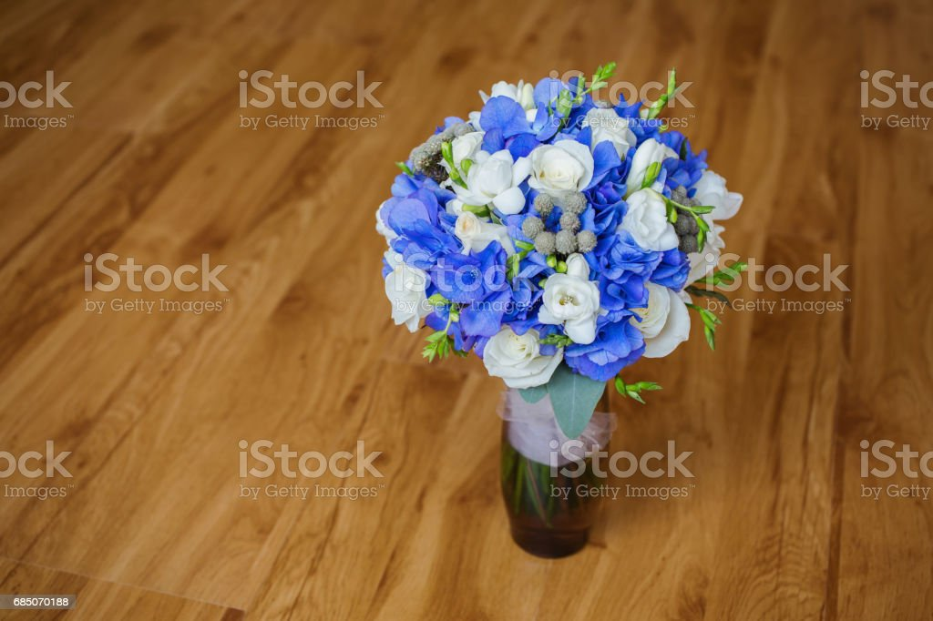 Wedding bouquet of white and blue flowers in a transparent vase stands on a light background. White Rose. Morning bride royalty-free stock photo