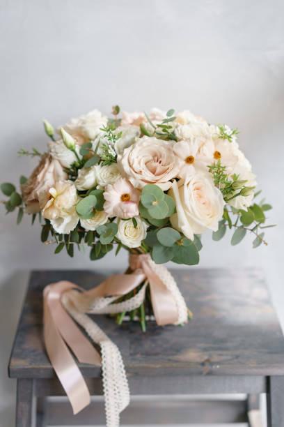 brautstrauß aus weißen rosen und butterblume auf einem holztisch. viel grün, zerzaust moderne asymmetrische braut haufen - brautstrauß aus holz stock-fotos und bilder