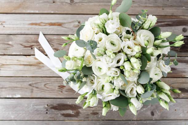 brautstrauß aus weißen rosen und ranunkeln auf einem holztisch. ansicht von oben. alte rustikale hintergrund - brautstrauß aus holz stock-fotos und bilder