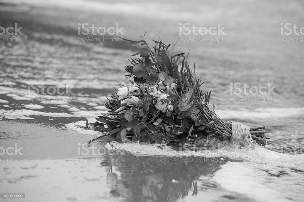 Wedding bouquet on the beach being washed away in waves stock photo
