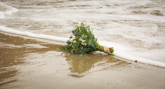 Wedding bouquet on the beach being washed away in waves