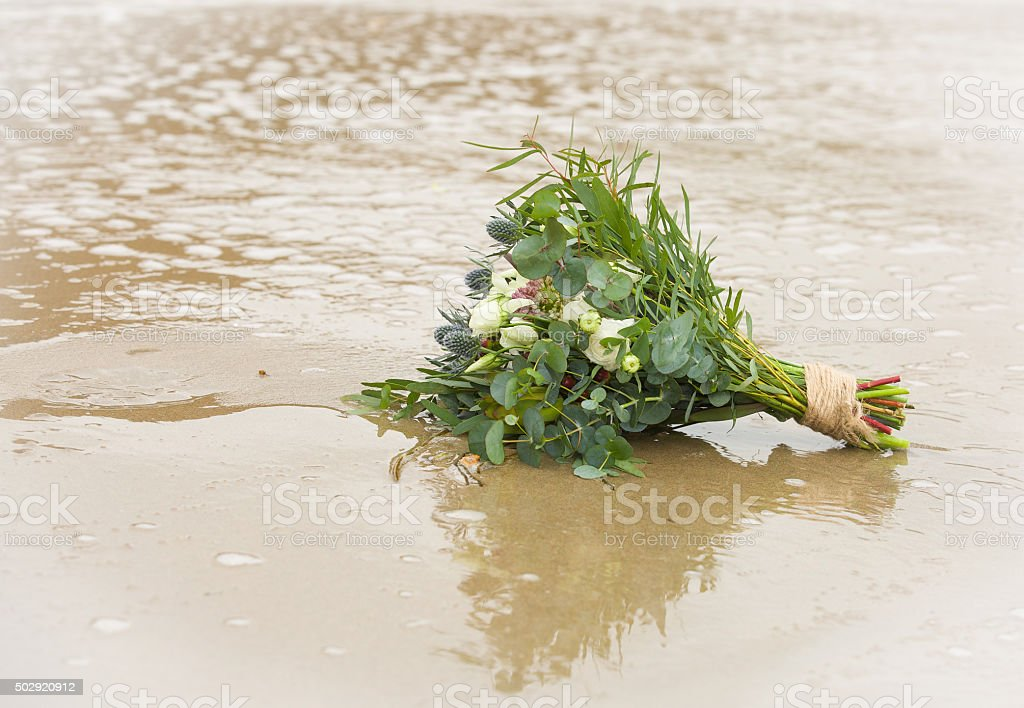 Wedding bouquet on the beach stranded on the sand stock photo