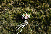 Wedding bridal bouquet lying on the grass in the field. flat lay. top view.