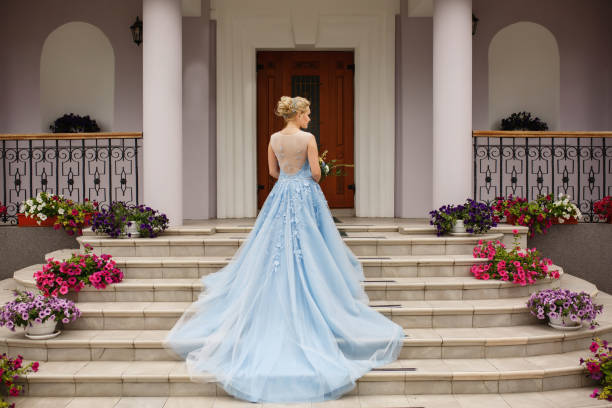 Wedding. Bride in blue wedding dress on stairs with flowers stock photo