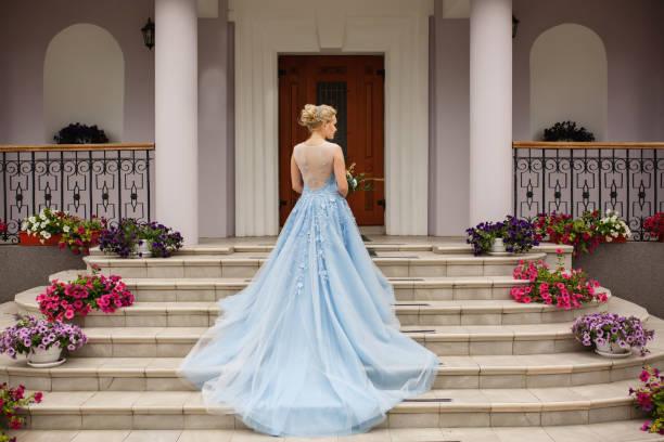 hochzeit. braut in blau brautkleid auf treppe mit blumen - verlobungskleider stock-fotos und bilder