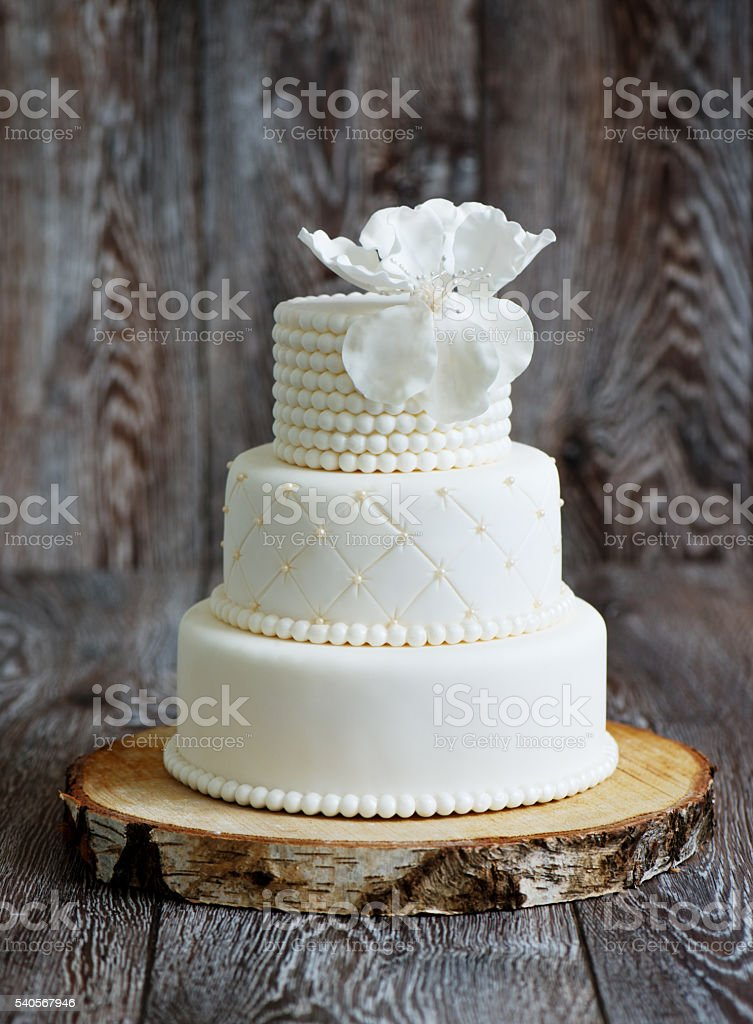 Wedding cake covered with white fondant stock photo