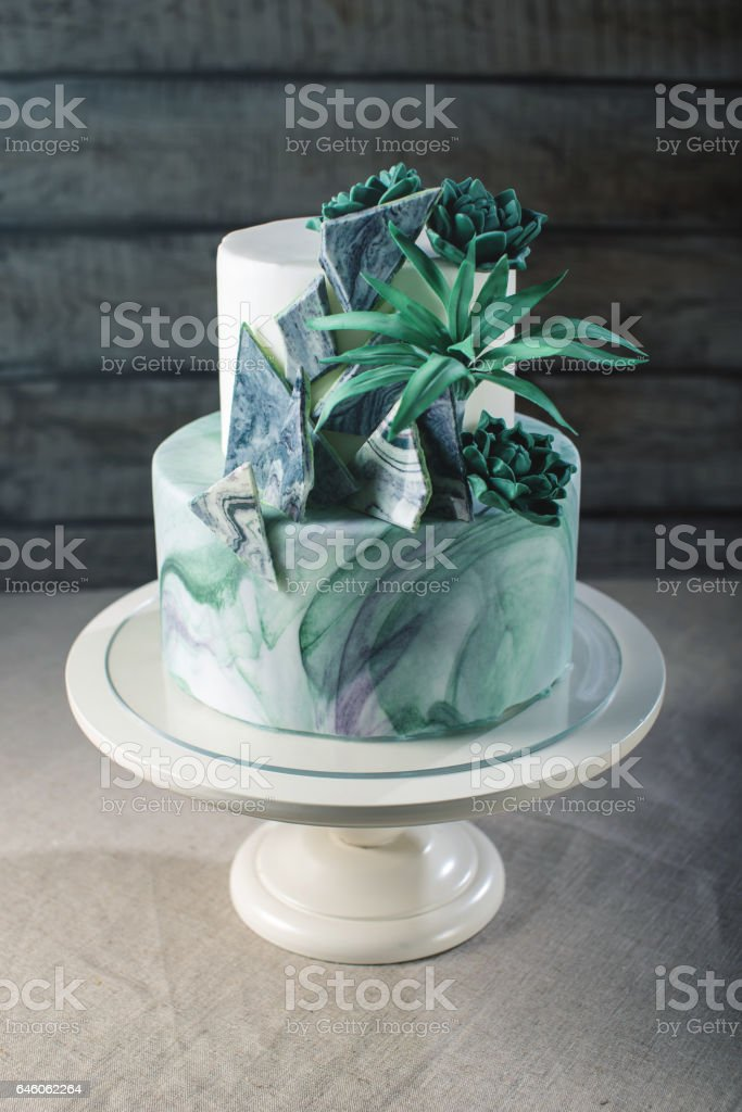 Wedding cake decorated like a stone marble with green flowers stock photo