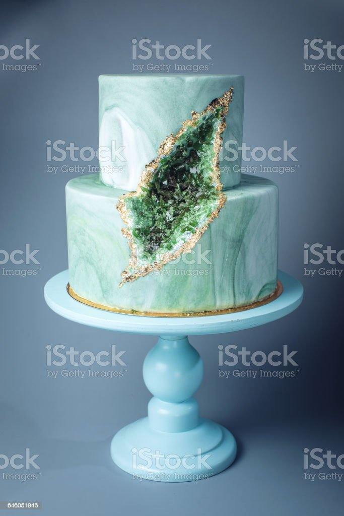 Wedding cake decorated like stone marble with emeralds in cut stock photo