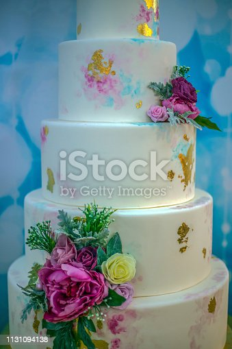 Wedding cake decorated with edible flowers and painted.