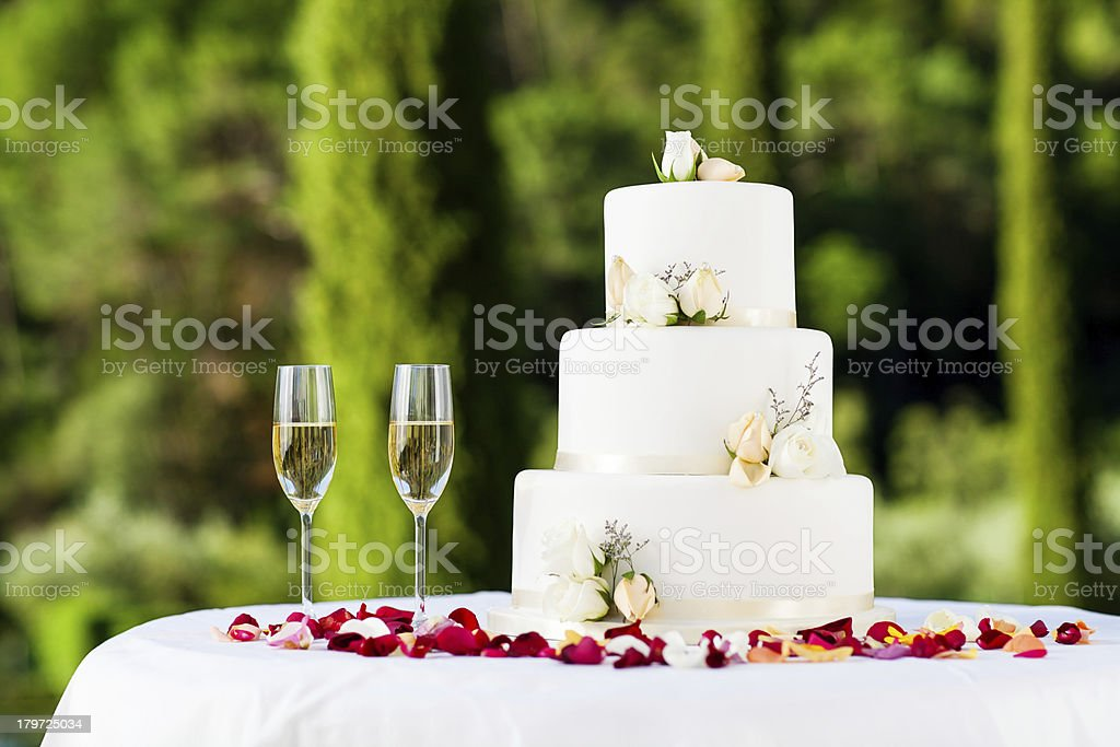 Wedding Cake Decorated With Flowers And Champagne Flutes On Table stock photo