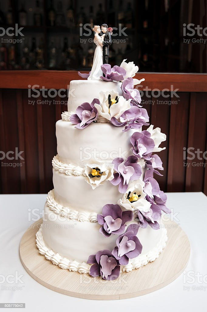 Wedding cake, decorated with purple flowers and figurines of bride...