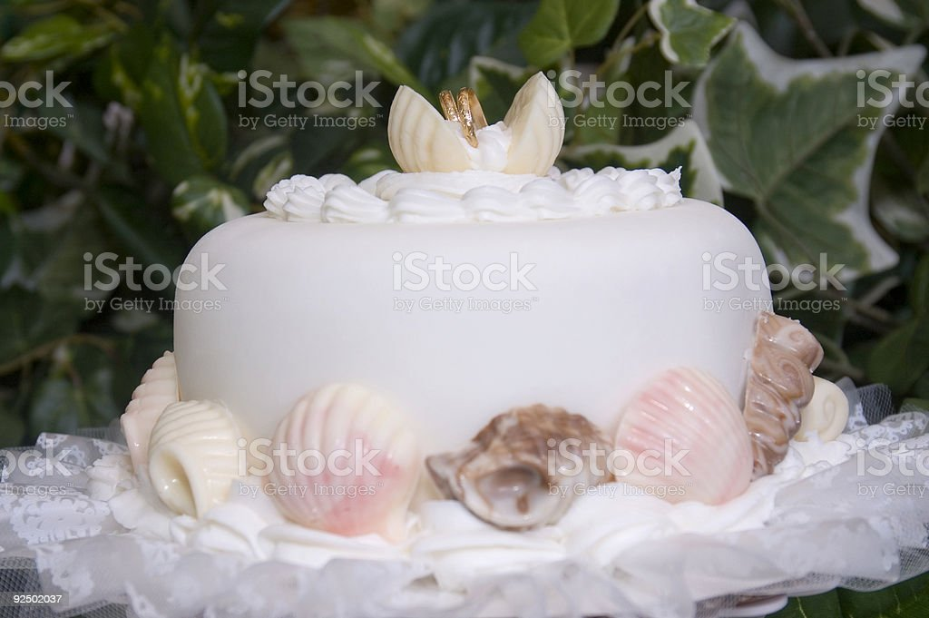 Wedding Cake Tier with Wedding Rings in Seashells royalty-free stock photo