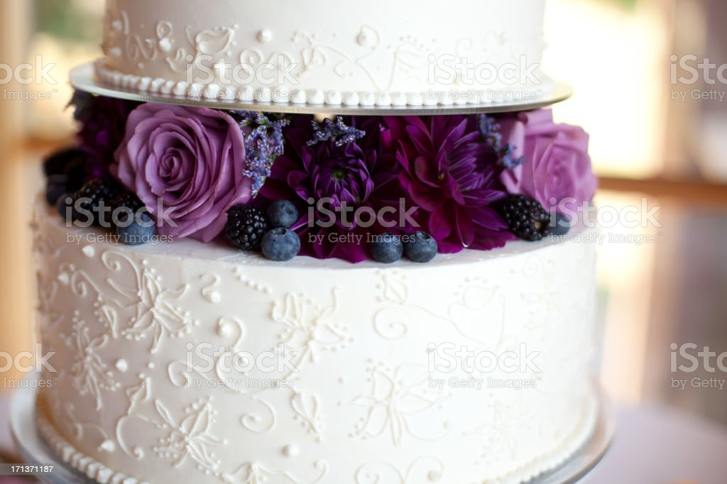 A layer of purple flowers between two layers of white wedding cake.