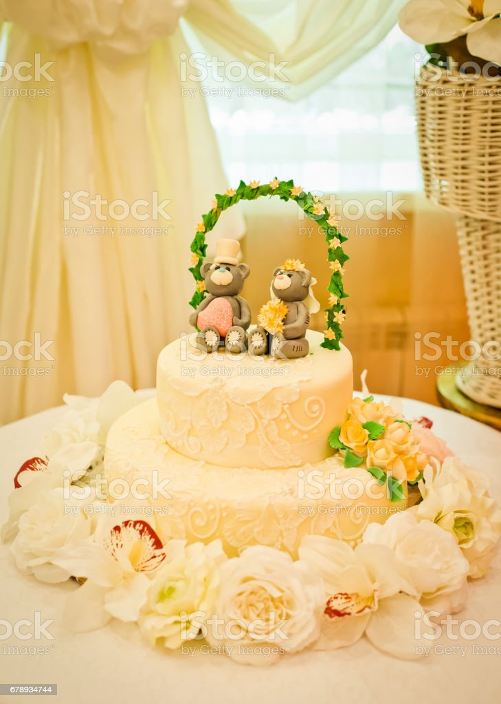 Wedding Cake With Teddy Bears On Top Sitting Under The Wedding Arch ...