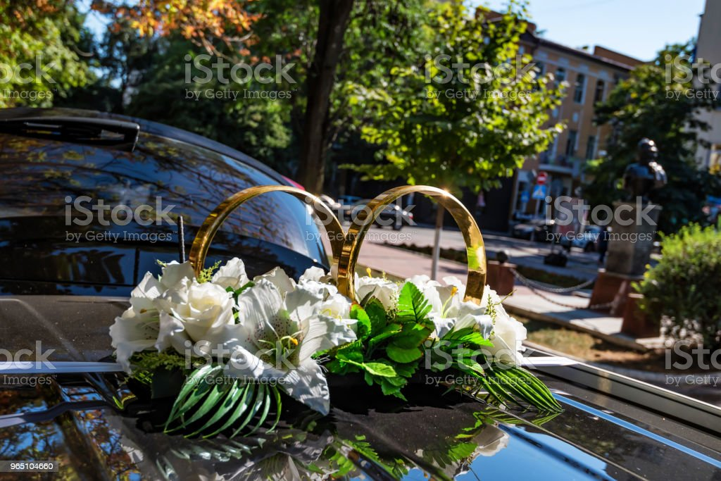 Wedding car decoration of rings and flowers royalty-free stock photo