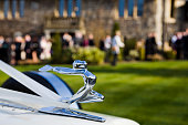 Bristol, England - March 19, 2011: Wedding Car Mascot with a ribbon infront of the venue. Grass lawn leads to the wedding guests mingling together