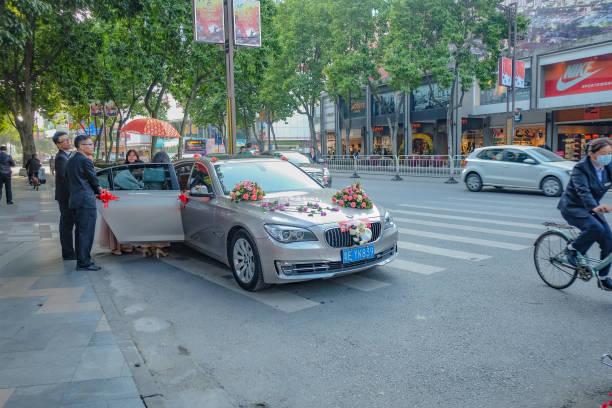 hochzeitsauto mit brautjungfer und brautführer foshan-stadt-china - brautjungfer kleid china stock-fotos und bilder