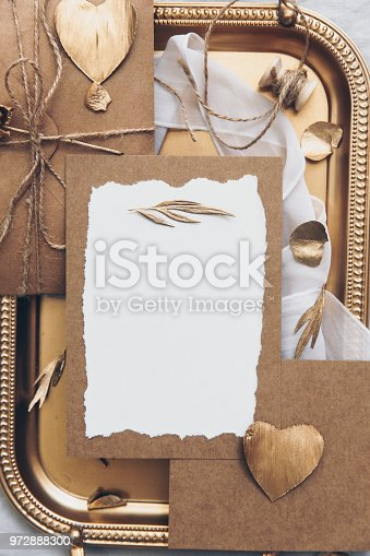 Wedding card invitation with decorations on gold tray