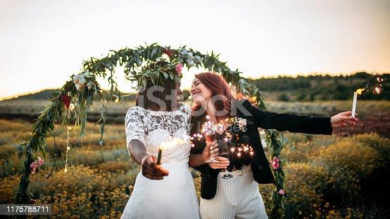 Lesbian wedding ceremony. Two brides celebrating lighting up sparklers and dancing