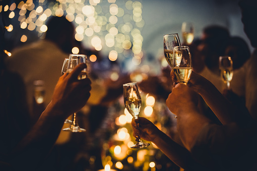 Numerous hands holding champagne flutes with champagne celebratory toast silhouettes