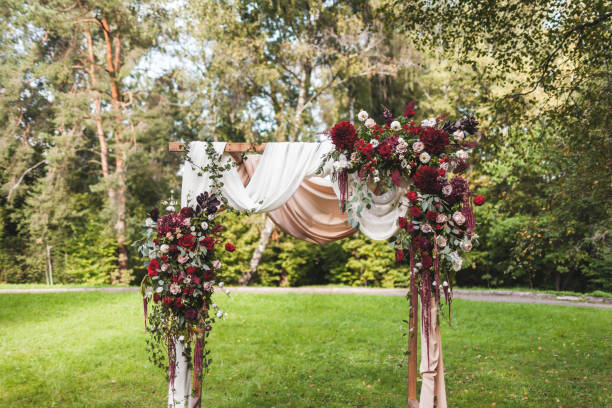 hochzeit zeremonie in rustikalem stil verziert mit roten blumen, weiße textil- und stühle im wald - grüne wald hochzeiten stock-fotos und bilder