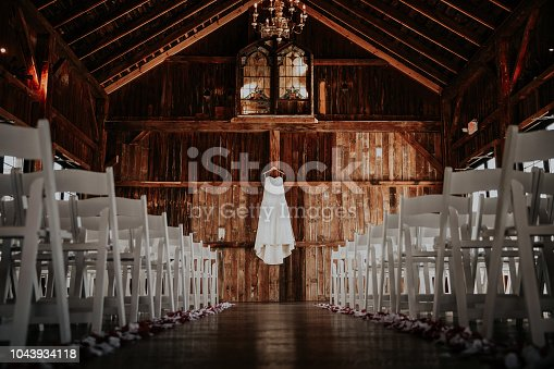 Barn wedding venue, set up for ceremony, with wedding dress hanging below stained glass