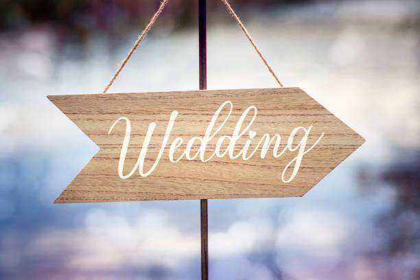 Wedding ceremony wooden arrow location sign stock photo
