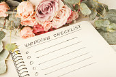 Wedding checklist with copy space and rose bouquet on the white desktop. Marriage planner concept, copy space.