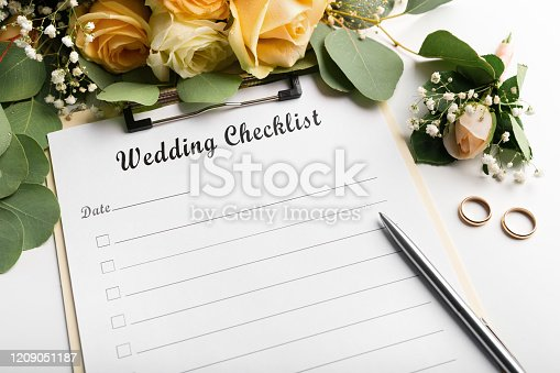Wedding checklist with copy space and cute flowers on the white desktop. Marriage planner concept
