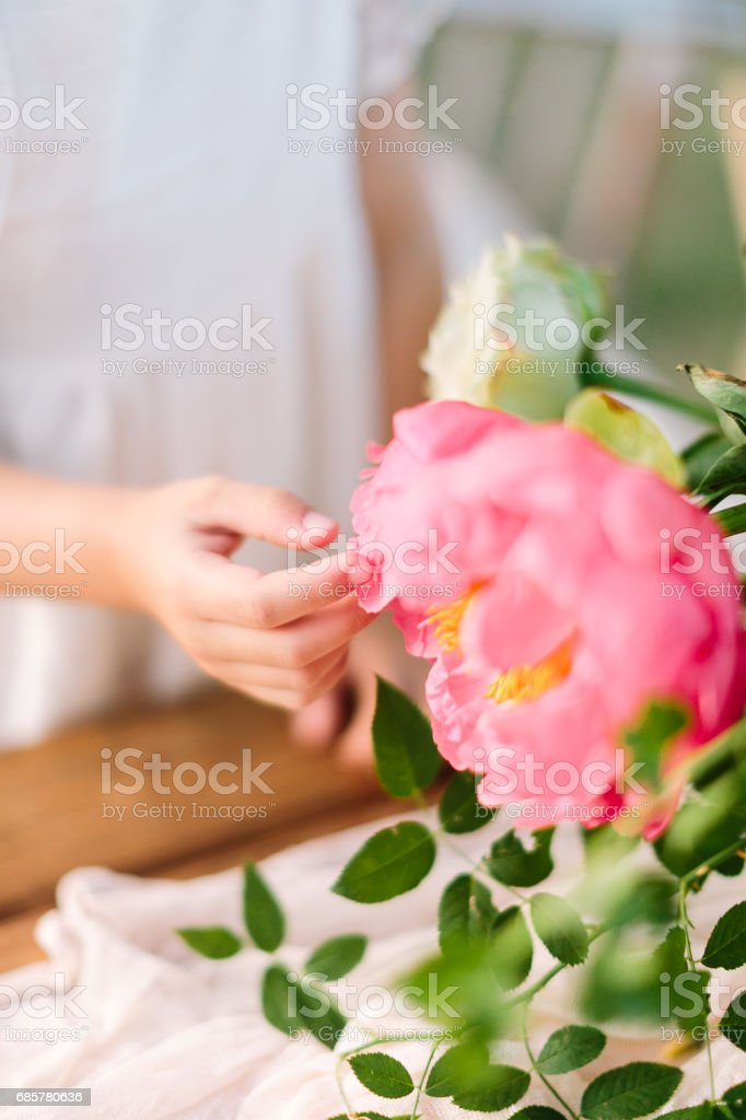 wedding, childcare, floral design, celebration, decoration concept - little soft hand of girl in white dress touching grand blooming bud of peony sorrounded by green leaves royalty-free stock photo