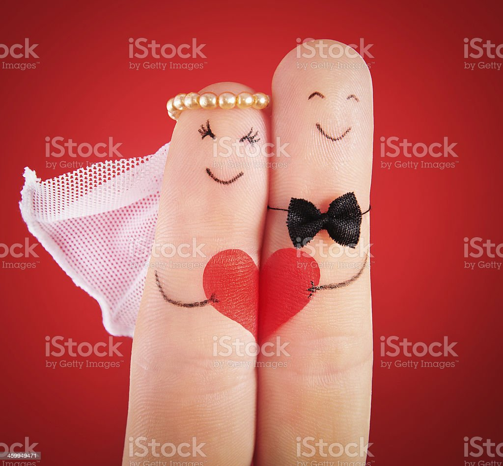 wedding concept - newlyweds painted at fingers against red stock photo