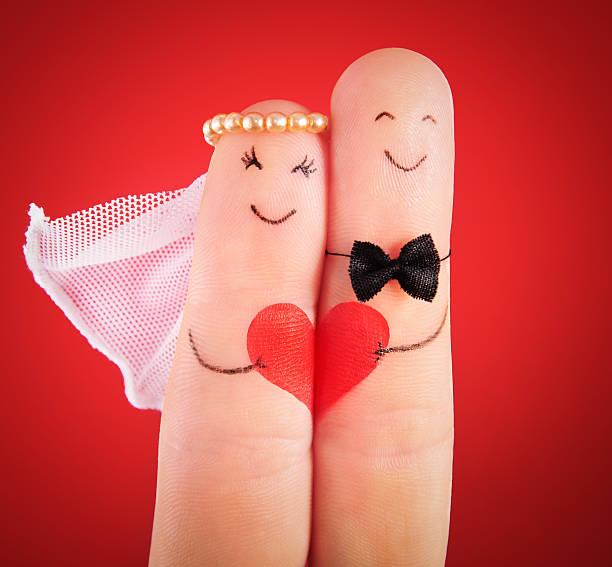 hochzeit-konzept-brautpaar gemalt an fingern gegen rot - verlobungsfeier einladungen stock-fotos und bilder