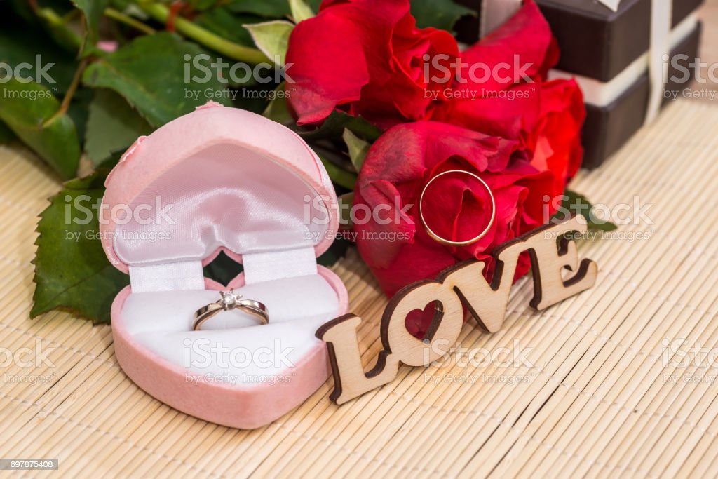 Wedding concept. text love with wedding rings, gift box and red roses