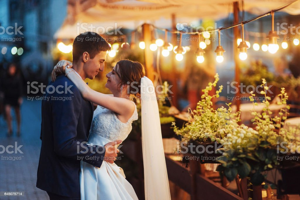 wedding couple at night lighting. Cafe along with decoration lig stock photo